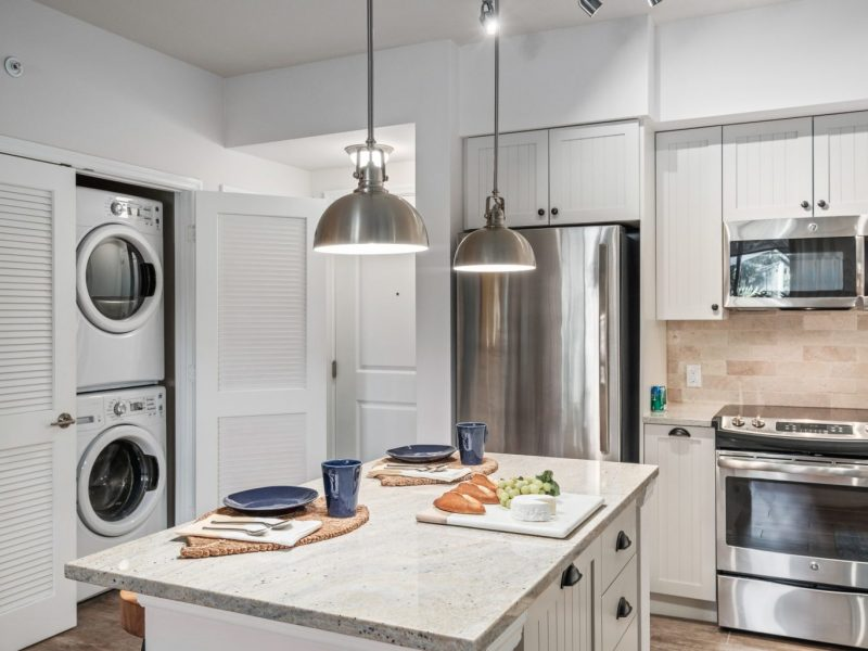 This image shows an expansive view of the Premium Apartment Feature, especially the kitchen island showcasing a neat granite-inspired countertop, accessible kitchen pieces of equipment, and an aisle directly through washer and dryer area.