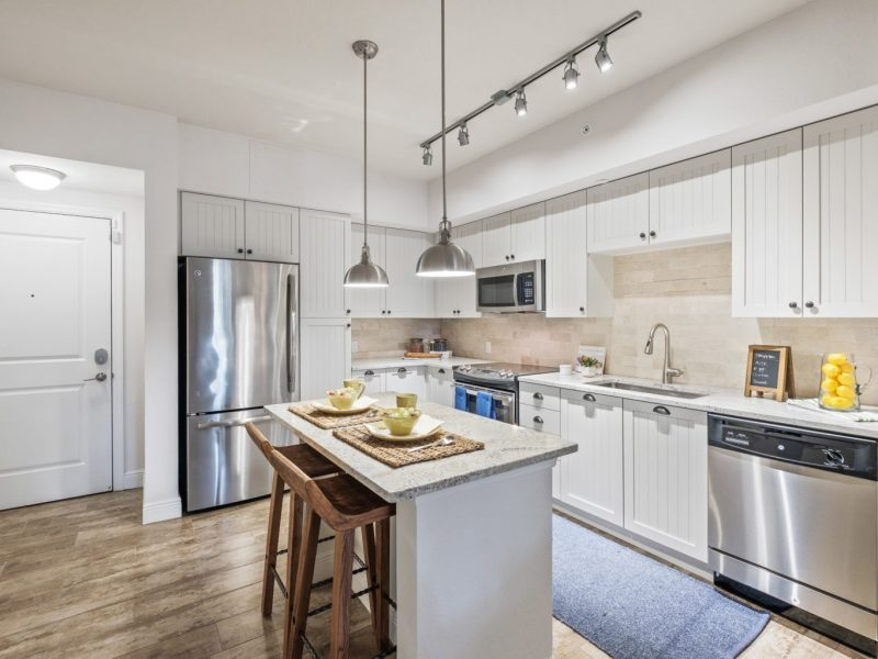 This image shows an expansive view of the kitchen island featuring kitchen pieces of equipment and quick access to the bathroom.