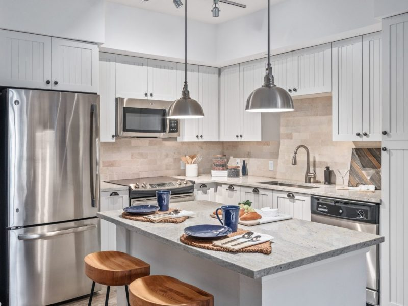 This image shows the Premium Apartment Feature, especially the kitchen island showcasing a granite-inspired countertop, a neat design, and accessible area through the bathroom.