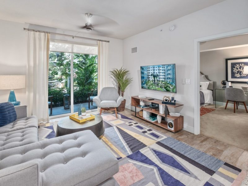 This image shows the Premium Apartment Feature, especially the living room area showcasing a spacious and luxurious interior design with a fireplace beside the private patio.