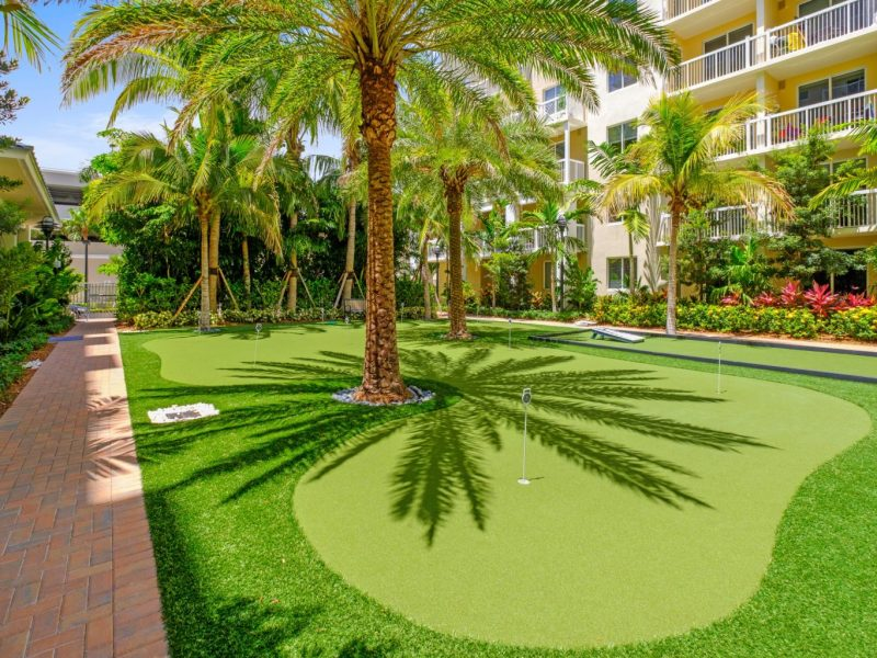 This image shows the TGM Harbor Beach Apartments Putting Green with a grassy golf fairway and lush trees that were a place for leisure and recreational activity.
