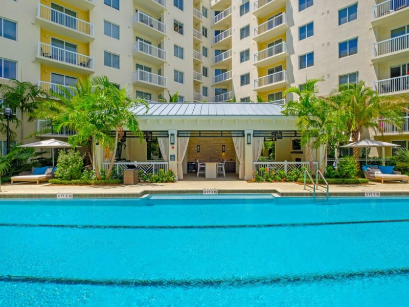 This image shows the resort-style outdoor swimming pool that is offering decent beds and luxurious cabanas nearby the swimming pool. The pool is not just giving a comfier facility but also handing out the beauty of its establishments.