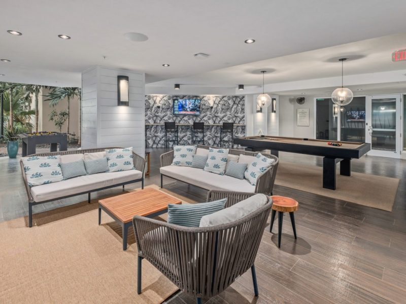 This image shows the TGM Harbor Beach Apartments TV Lounge featuring a spacious billiard table and a comfy sitting area while watching on a movie treat.